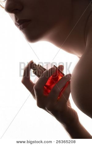 sensual woman applying perfume on her body, bright red perfume bottle
