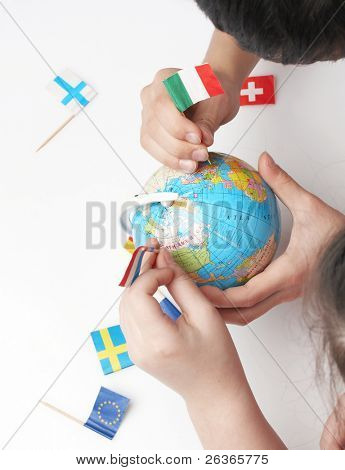 children pointing flags on world globe