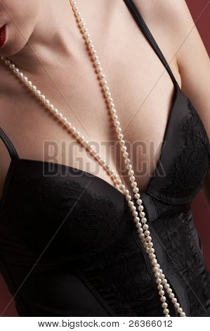 close-up of a woman wearing black corset and long pearls