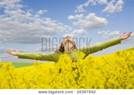 girl spreading her arms in the middle of a rapeseed field with blue cloudy sky, 'outdoor freedom'