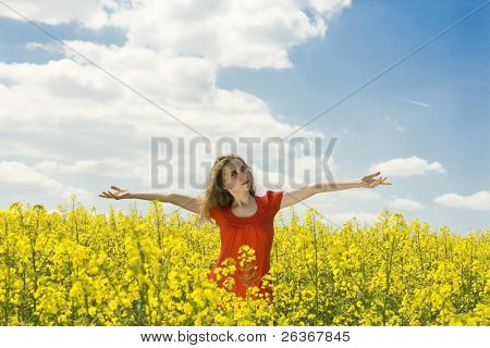 beautiful girl spreading her arms in the middle of a rapeseed(canola) field with blue cloudy sky, 'outdoor freedom'