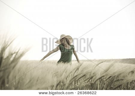 blond girl with big hat in a green wheat field enjoying nature