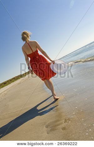 woman in red dress holding white hat walking on the beach