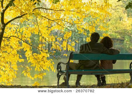 romantic couple on a bench by the lake in autumn