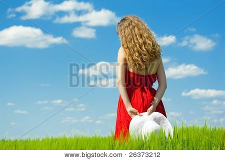 summertime; woman in red dress standing on green field over blue sky