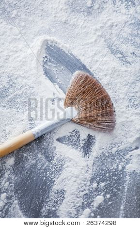 thick professional fan brush and loose white powder particles scattered around