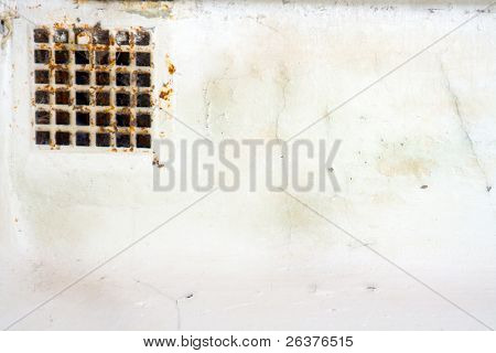 Rusty air grating and wall with whitewashing and sagging