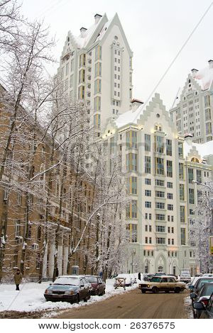 City in winter: snow-covered trees, cars, roadway and white multistorey building at the end of the street