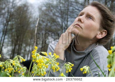 Žena leží na přírodu poblíž primula květiny a snění.