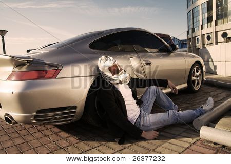 Sick man in gas mask sitting near expensive car at parking in the city