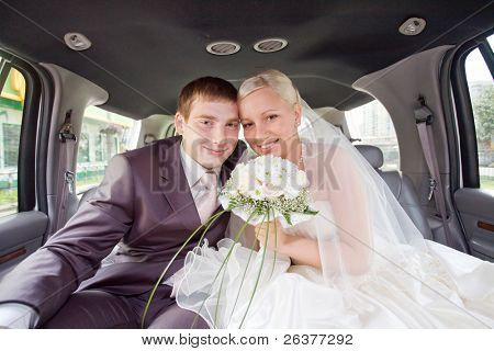 Smiling newlyweds inside the limo