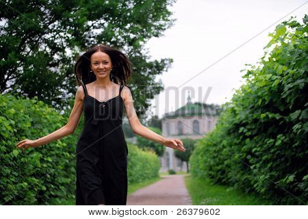 Young beautiful woman wearing black dress is walking with arms opened wide through the park near the palace.