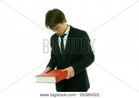 One young good-looking man, wearing eyeglasses and lounge suit is looking at a red big book that he has in his hands.