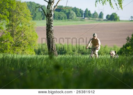 50 years old woman at bicycle with alsatian dog