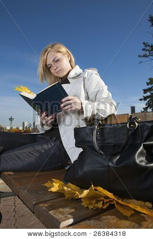 Woman reading a book in autumnal park
