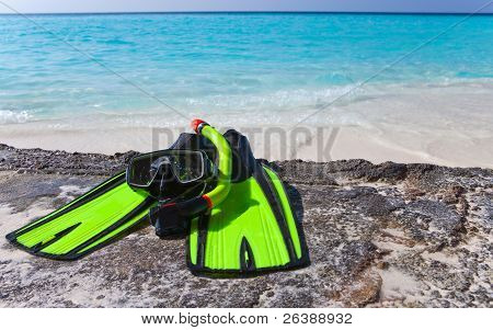 Accessory for Snorkeling -mask flippers tube-lay on sand on background of ocean