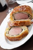 foto of beef wellington  - Slices of rare Beef Wellington on the serving dish - JPG