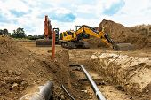 Installation Of New Gas Pipes On A Building Site With A View Down The Open Trench And Heavy Duty Mac poster