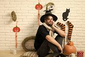 Halloween Man Smiling In Witch Hat. Macho Sitting With Gift Box And Cups On Floor. Pumpkins, Stockin poster