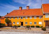 Ochre coloured historic building on old Stavern market square (Torvet). Stavern is a popular travel  poster