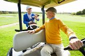 Senior man sitting in golf car while talking to his buddy preparing golf clubs behind poster