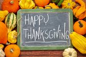 Happy Thanksgiving  - white chalk handwriting on a slate blackboard surrounded by winter squash and  poster