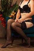 Woman Dressing Stockings Sitting In A Chair. Beautiful Female Legs In Black Stockings poster