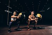 Athletic Sportsman And Sportswoman Exercising With Medicine Balls Together In Dark Gym poster