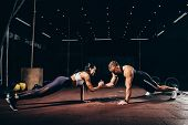 Athletic Sportsman And Sportswoman Doing Push Ups Together And Holding Hands In Dark Gym poster