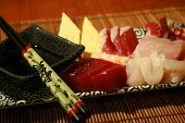 picture of yellowfin tuna  - A plate of sashimi (slices of raw fish) with chopsticks and a dish of soy sauce.