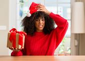 African american woman holding present wearing christmas red hat stressed with hand on head, shocked poster