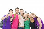group of teenagers taking pictures of themselves with their mobile phones