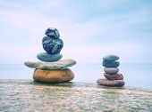 Stack Of Stones On The Sea Beach. Rounded Pebbles Stack In Peaceful Evening With Smooth Ocean Backgr poster