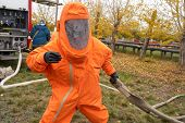 A Man Works In An Orange Chemical Protection Suit. Chemical Hazards. poster