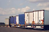 Modern Trucks Of Various Models Are In A Row On Truck Stop. Back View. poster