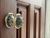 Close Up Vintage Brass Door Knob With Ornament On Red Wood Polished Door poster