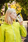Young Woman Drinking Water. Beauty Girl Drinking Water From Glass On Nature Background. Face Portrai poster