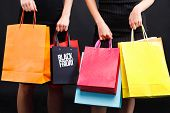 Two Girls Wearing Black Dresses Holding Many Colorful Shopping Bags On The Black Background, Black F poster
