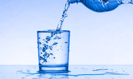 foto of drinking water  - Drinking water is poured from a bottle into a glass - JPG