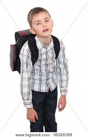 Schulkind mit einer schweren Ranzen auf Schultern.