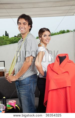 Portrait of multiethnic male and female fashion designers standing together beside mannequin