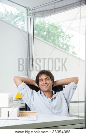 Happy young male architect looking at model house while sitting in chair with hands behind head
