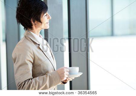 smart middle aged businesswoman having coffee break in office