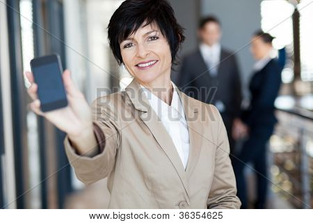 happy middle aged businesswoman showing smart phone