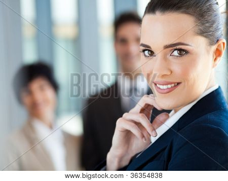 attractive young businesswoman closeup portrait with co-workers in background