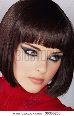beautiful young woman with short brown hair in red blouse wearing smoky purple eyeshadow and dramatic eyeliner.