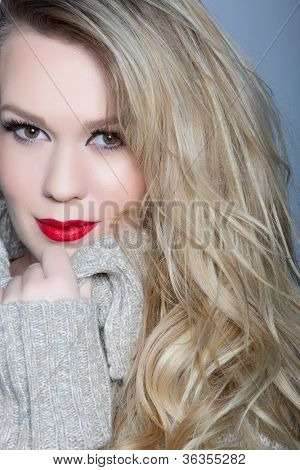 portrait of a beautiful young woman with curly blond hair and glamour make-up with red lips wearing a gray knit sweater