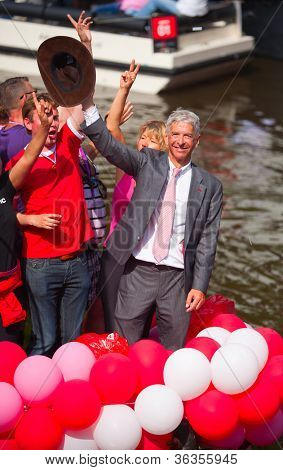 AMSTERDAM, THE NETHERLANDS - AUGUST 4: Politician Ronald Plassterk in front of spectators at the famous Canal Parade of the Amsterdam Gay Pride 2012 on August 4, 2012 in Amsterdam
