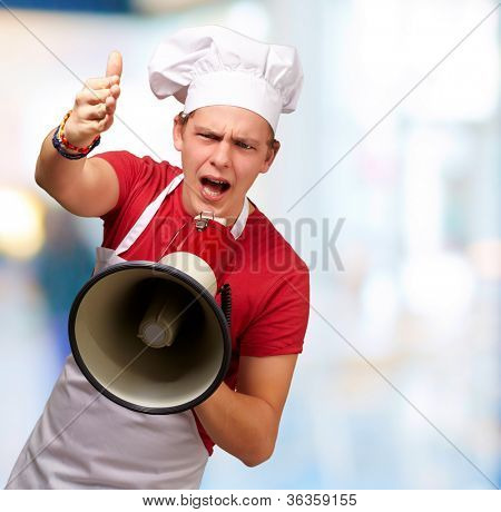 portrait of young cook man screaming with megaphone and gesturing against a nature background