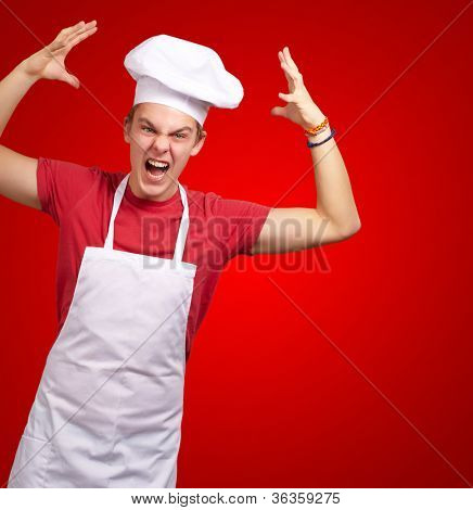 Angry Young Man Raising His Hand On Red Background